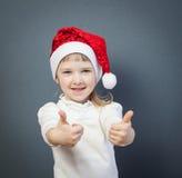 Niña sonriente en el sombrero de Papá Noel que muestra los pulgares para arriba imagenes de archivo