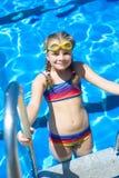 Niña sonriente en gafas de la natación en la piscina Imagen de archivo libre de regalías
