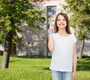 Niña sonriente en la camiseta en blanco blanca Imagenes de archivo