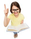 Niña sonriente en lentes con el libro Imagen de archivo