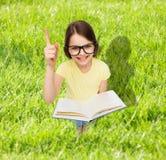 Niña sonriente en lentes con el libro Fotografía de archivo libre de regalías