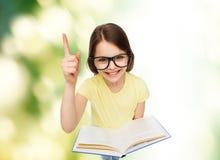 Niña sonriente en lentes con el libro Foto de archivo libre de regalías
