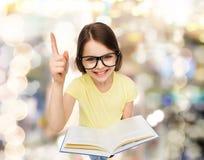 Niña sonriente en lentes con el libro Imágenes de archivo libres de regalías