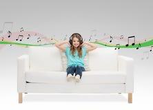 Niña sonriente en los auriculares que se sientan en el sofá Foto de archivo libre de regalías