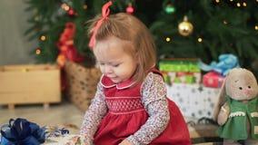 Niña sonriente en los sundress rojos que sostienen una muñeca hecha punto en sus manos cerca del árbol de navidad Primer almacen de metraje de vídeo