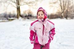Niña sonriente en nieve imagenes de archivo