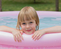 Niña sonriente en piscina inflable Imagen de archivo libre de regalías