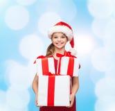 Niña sonriente en sombrero del ayudante de santa con los regalos Fotografía de archivo libre de regalías