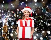 Niña sonriente en sombrero del ayudante de santa con los regalos Imagen de archivo