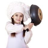 Niña sonriente en sombrero del cocinero con el sartén Imagenes de archivo