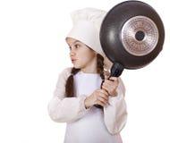 Niña sonriente en sombrero del cocinero con el sartén Imágenes de archivo libres de regalías