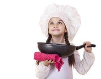 Niña sonriente en sombrero del cocinero con el sartén Fotos de archivo