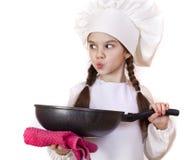 Niña sonriente en sombrero del cocinero con el sartén Imagen de archivo
