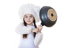 Niña sonriente en sombrero del cocinero con el sartén Fotografía de archivo libre de regalías