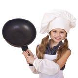 Niña sonriente en sombrero del cocinero con el sartén Fotografía de archivo