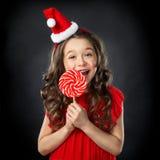 Niña sonriente en sombrero del ` s de santa con el caramelo, fondo oscuro aislado Imagen de archivo