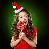 Niña sonriente en sombrero del ` s de santa con el caramelo, fondo verde aislado Foto de archivo libre de regalías