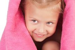 Niña sonriente envuelta en una toalla rosada Foto de archivo