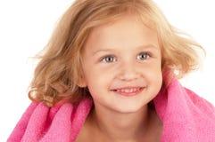 Niña sonriente envuelta en una toalla rosada Imágenes de archivo libres de regalías