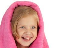 Niña sonriente envuelta en una toalla rosada Fotos de archivo libres de regalías