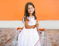 Niña sonriente feliz en carro de la compra con helado sabroso Fotos de archivo libres de regalías