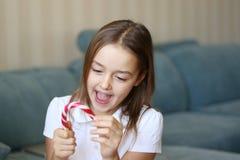 Niña sonriente feliz hermosa que sostiene el bastón de caramelo de la Navidad y que lo mira feliz y excitado imágenes de archivo libres de regalías