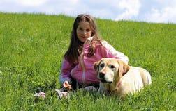 Niña sonriente hermosa con el perro de Labrador Foto de archivo libre de regalías