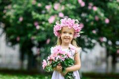 Niña sonriente linda con la guirnalda de la flor en el parque Retrato del peque?o ni?o adorable al aire libre midsummer D?a de ti foto de archivo libre de regalías