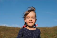 Niña sonriente linda debajo del cielo azul claro fotografía de archivo