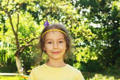 Niña sonriente linda en el fondo del parque de la ciudad Fotografía de archivo