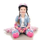 Niña sonriente linda en pcteres de ruedas rosados fotografía de archivo