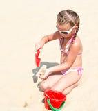 Niña sonriente linda que juega en la playa Imagenes de archivo