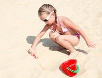Niña sonriente linda que juega en la playa Imágenes de archivo libres de regalías