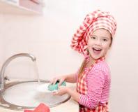 Niña sonriente linda que lava los platos Foto de archivo