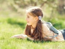 Niña sonriente linda que miente en la hierba Fotos de archivo libres de regalías