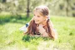 Niña sonriente linda que miente en la hierba Imagenes de archivo