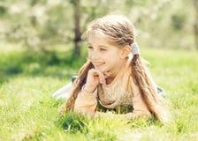 Niña sonriente linda que miente en la hierba Imágenes de archivo libres de regalías