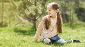 Niña sonriente linda que se sienta en la hierba Imágenes de archivo libres de regalías
