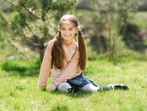 Niña sonriente linda que se sienta en la hierba Fotos de archivo