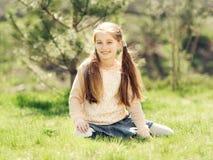 Niña sonriente linda que se sienta en la hierba Imagen de archivo libre de regalías