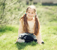 Niña sonriente linda que se sienta en la hierba Foto de archivo libre de regalías