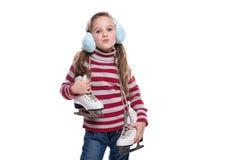Niña sonriente preciosa que lleva el suéter colorido y el tocado rayados, sosteniendo patines aislados en el fondo blanco Fotos de archivo libres de regalías