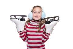Niña sonriente preciosa que lleva el suéter colorido y el tocado rayados, sosteniendo patines aislados en el fondo blanco Clo del Foto de archivo libre de regalías