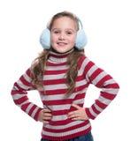 Niña sonriente preciosa que lleva el suéter rayado colorido y tocado aislado en el fondo blanco Ropa del invierno Imagen de archivo