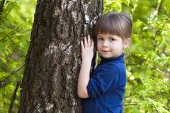 Niña sonriente preciosa que se coloca cerca de árbol grande en hierba verde Fotos de archivo libres de regalías