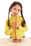 Niña sonriente que come el encadenamiento de salchichas Imagen de archivo