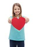 Niña sonriente que da el corazón rojo Foto de archivo
