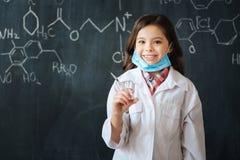 Niña sonriente que disfruta de la clase de la medicina en la escuela Imagen de archivo