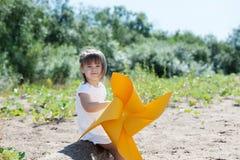 Niña sonriente que juega con el molino de viento Foto de archivo