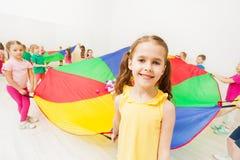 Niña sonriente que juega a juegos del paracaídas en gimnasio Imágenes de archivo libres de regalías